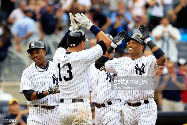 Robinson Cano of the New York Yankees is congratulated by his teammates Curtis Granderson Alex Rodriguez and Derek Jeter for his grand slam home run...