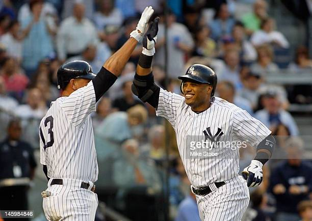 Robinson Cano of the New York Yankees is congratulated by teammate Alex Rodriguez after hitting his second homerun of the game during the thirdinning...