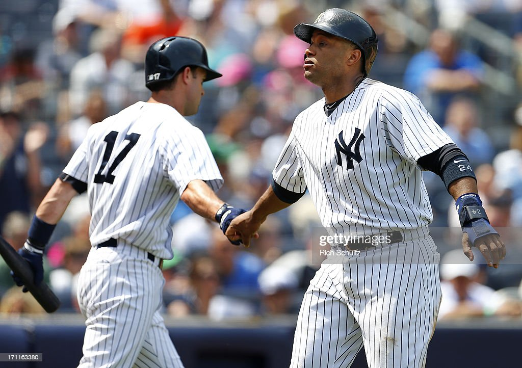 Robinson Cano #24 of the New York Yankees is congratulated by teammate Jayson Nix #17 after scoring on a single by Zoilo Almonte #45 in the third inning against the Tampa Bay Rays at Yankee Stadium on June 22, 2013 in the Bronx borough of New York City. The Yankees defeated the Rays 7-5.