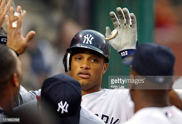 Robinson Cano of the New York Yankees is congratulated by teammates after scoring in the first inning of a 86 loss to the Los Angeles Angels of...