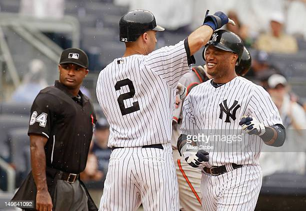 Robinson Cano of the New York Yankees is greeted by Derek Jeter after connecting on a fourthinning grand slam against the Baltimore Orioles at Yankee...