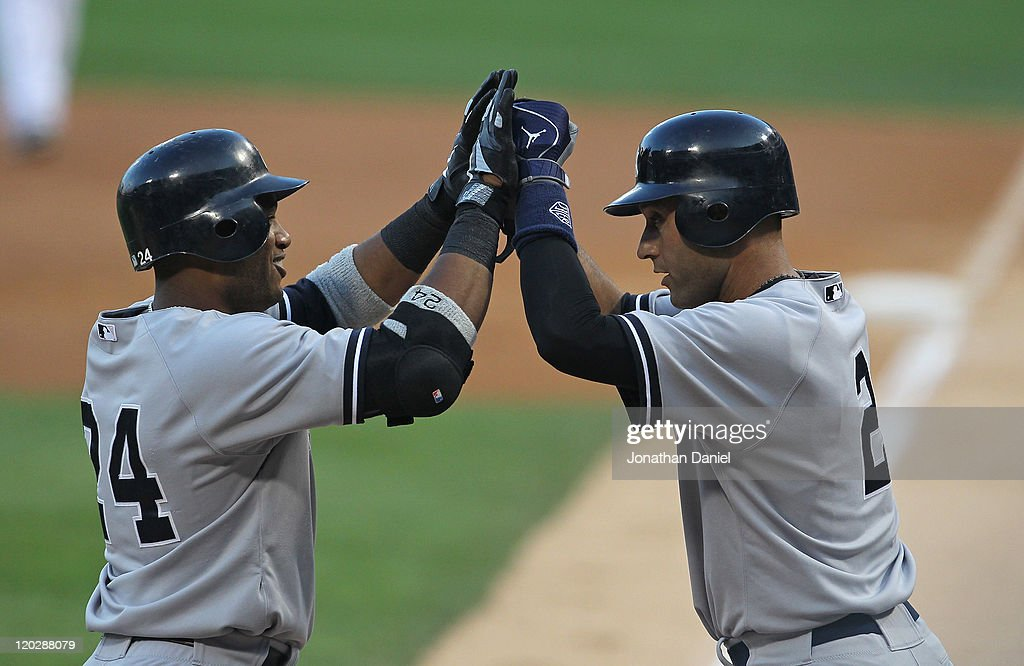 Robinson Cano #24 of the New York Yankees is greeted by teammate Derek Jeter #2 after hitting a three-run home run in the 1st inning against the Chicago White Sox at U.S. Cellular Field on August 3, 2011 in Chicago, Illinois.