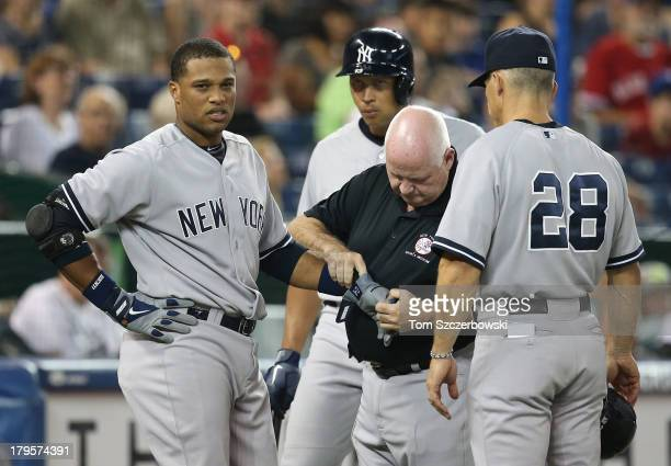 Robinson Cano of the New York Yankees reacts after being hit by pitch in the first inning as trainer Steve Donohue and Alex Rodriguez and manager Joe...