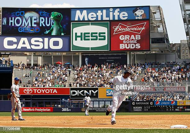 Robinson Cano of the New York Yankees rounds the bases on his threerun home run against the Toronto Blue Jays during the first game of a double...