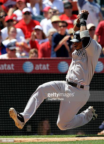 Robinson Cano of the New York Yankees slides into home to score on a Francisco Cervelli single in the fourth inning against the Los Angeles Angels of...