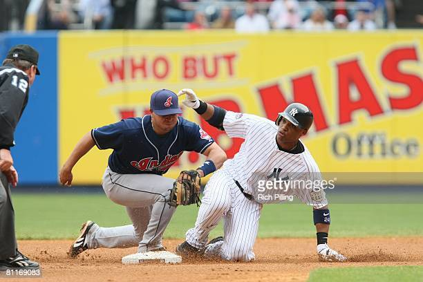 Robinson Cano of the New York Yankees slides safely into second base during the game against the Cleveland Indians at the Yankee Stadium in the...