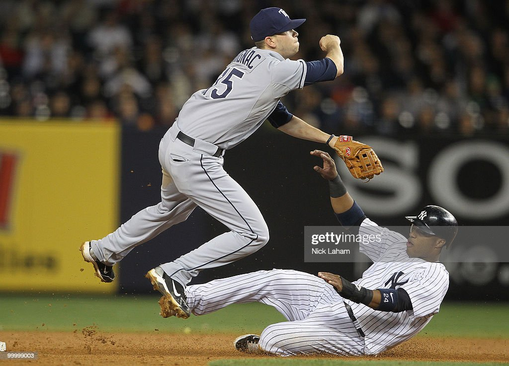 Robinson Cano #24 of the New York Yankees slides under Reid Brignac #15 of the Tampa Bay Rays as he turns a doule play at Yankee Stadium on May 19, 2010 in the Bronx borough of New York City.