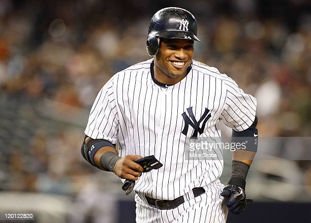 Robinson Cano of the New York Yankees smiles after he hits a double and drives in his fifth run of the game against the Baltimore Orioles on July 30...