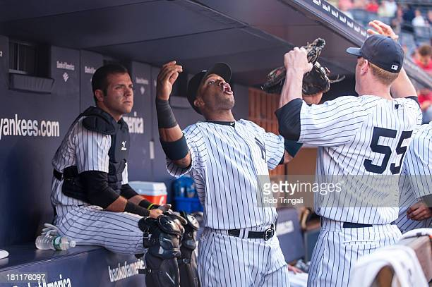 Robinson Cano of the New York Yankees stretches in the dugout with Lyle Overbay during the game against the New York Mets at Yankee Stadium on May 30...