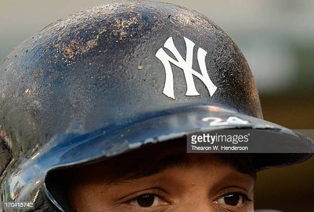 Robinson Cano of the New York Yankees with his batting helmet covered with pinetar looks on from the dugout against the Oakland Athletics at Oco...