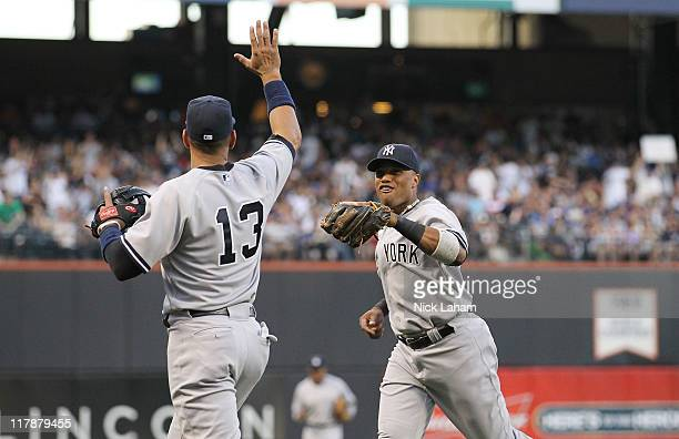 Robinson Cano of the of the New York Yankees celebrates an inning ending play with teammate Alex Rodriguez against the New York Mets at Citi Field on...