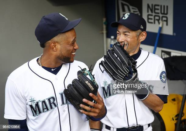 Robinson Cano of the Seattle Mariners and Ichiro Suzuki share a laugh in the dugout before the game against the Oakland Athletics at Safeco Field on...