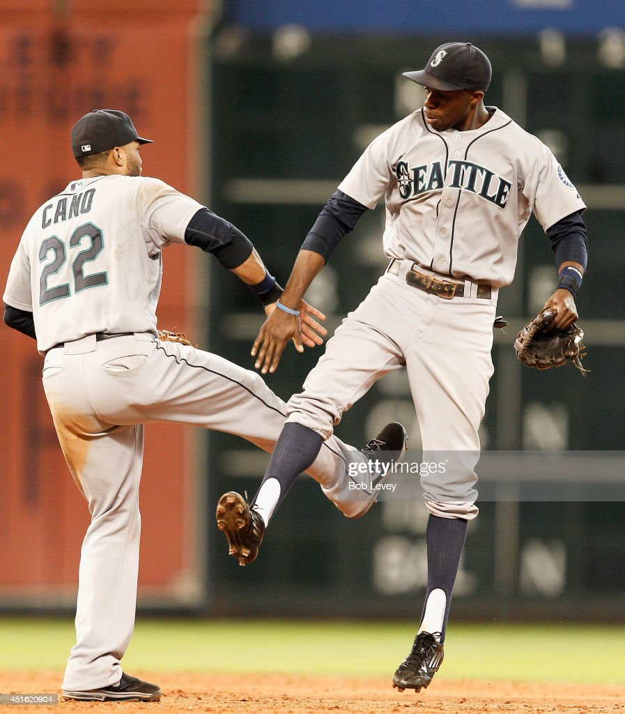 Robinson Cano #22 of the Seattle Mariners and James Jones #99 celebrate after the final out as the Seattle Mariners defeated the Houston Astros 5-2 at Minute Maid Park on July 2, 2014 in Houston, Texas.