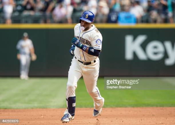 Robinson Cano of the Seattle Mariners blows a bubble as he rounds the bases after hitting a tworun home run off of starting pitcher Daniel Gossett of...