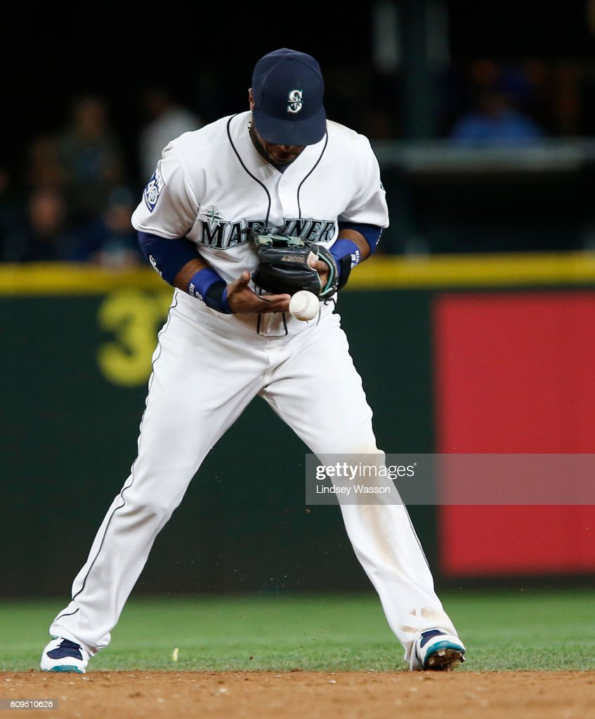 Robinson Cano #22 of the Seattle Mariners bobbles the ball, allowing Lorenzo Cain #6 of the Kansas City Royals to reach first base on his error in the tenth inning at Safeco Field on July 5, 2017 in Seattle, Washington.