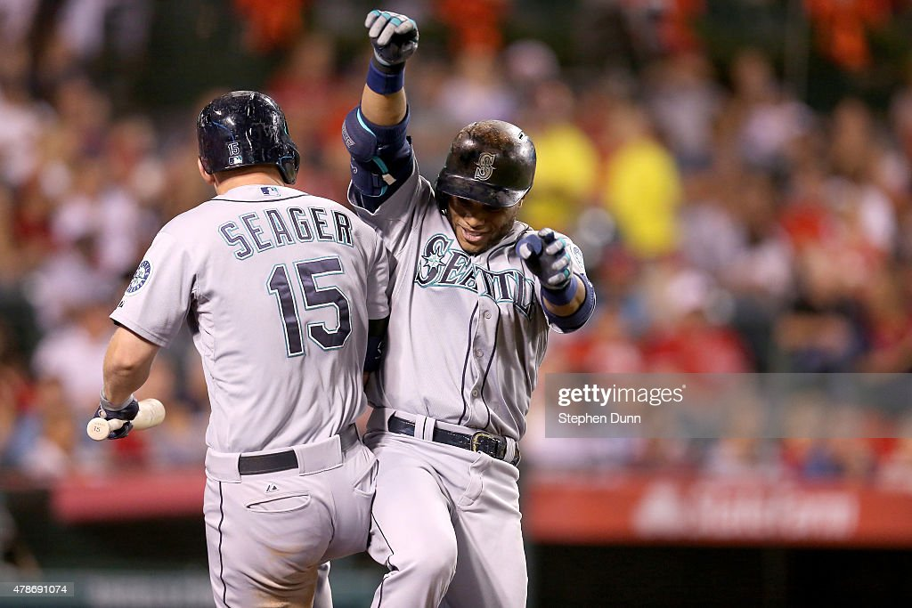Robinson Cano #22 of the Seattle Mariners celebrates with on deck hitter Kyle Seager #15 as he returns to the dugout after hitting a solo home run in the eighth inning against the Los Angeles Angels of Anaheim at Angel Stadium of Anaheim on June 26, 2015 in Anaheim, California.