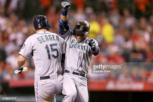 Robinson Cano of the Seattle Mariners celebrates with on deck hitter Kyle Seager as he returns to the dugout after hitting a solo home run in the...