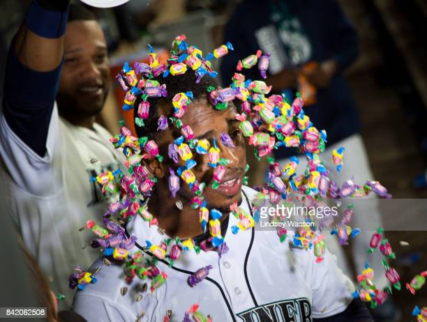 Robinson Cano of the Seattle Mariners dumps a bucket of bubble gum over Jean Segura during a postgame interview after Segura scored the winning run...