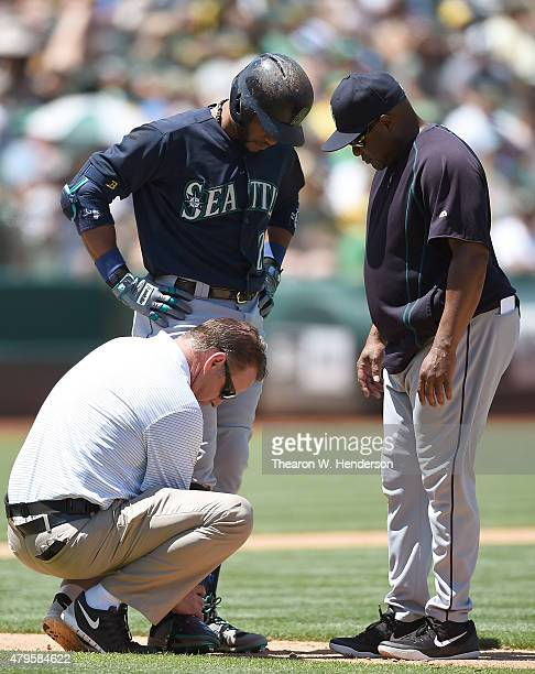 Robinson Cano of the Seattle Mariners gets looked at by assistant trainer Rob Nodine and manager Lloyd McClendon after Cano was hit in the foot by a...
