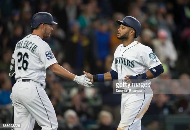 Robinson Cano of the Seattle Mariners is congratulated by Danny Valencia after Cano scored on a sacrifice fly off the bat of Kyle Seager against...