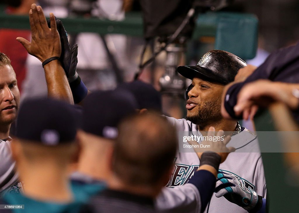 Robinson Cano #22 of the Seattle Mariners is greeted as he returns to the dugout after hitting a solo home run in the eighth inning against the Los Angeles Angels of Anaheim at Angel Stadium of Anaheim on June 26, 2015 in Anaheim, California.