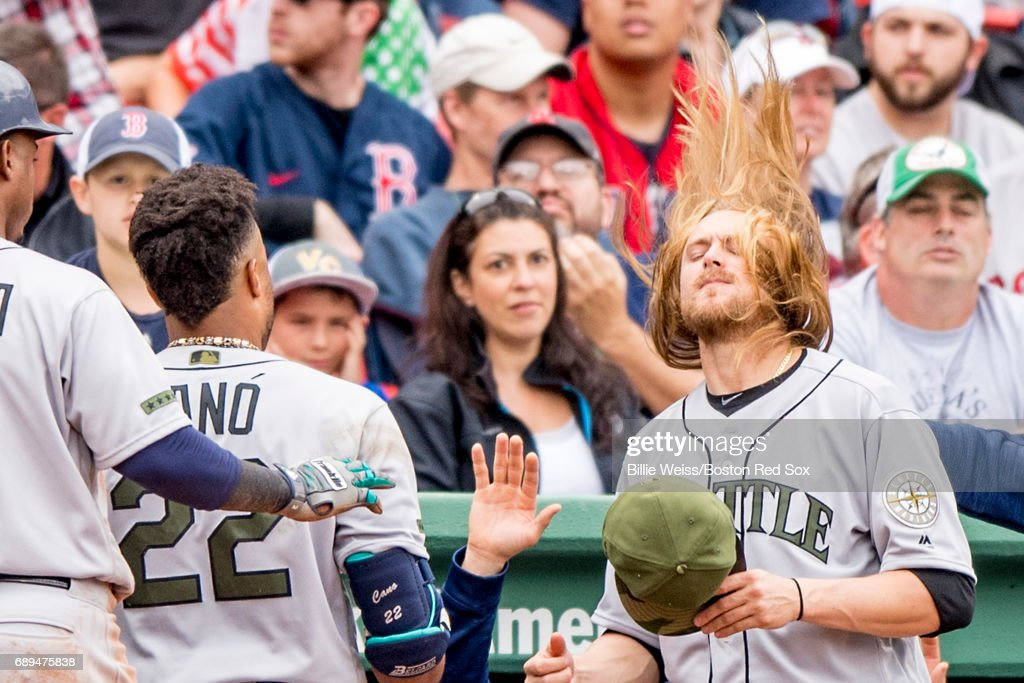 Robinson Cano #22 of the Seattle Mariners reacts with Jean Segura #2 and Taylor Motter #21 after hitting a two run home run during the ninth inning of a game against the Boston Red Sox on May 28, 2017 at Fenway Park in Boston, Massachusetts.