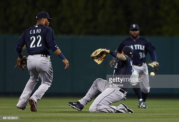 Robinson Cano Stefen Romero and Abraham Almonte of the Seattle Mariners can't make the catch on a ball hit by Hank Conger of the Los Angeles Angels...