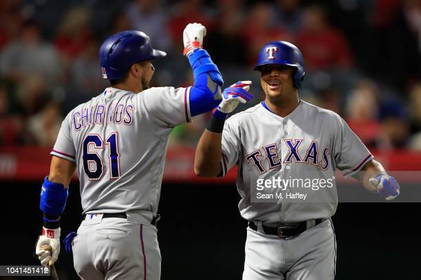 Robinson Chirinos congratulates Adrian Beltre of the Texas Rangers after his solo homerun during the second inning of a game against the Los Angeles...