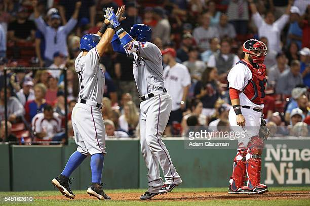 Robinson Chirinos high fives Rougned Odor of the Texas Rangers after hitting a three run home run in the ninth inning of the game against the Boston...