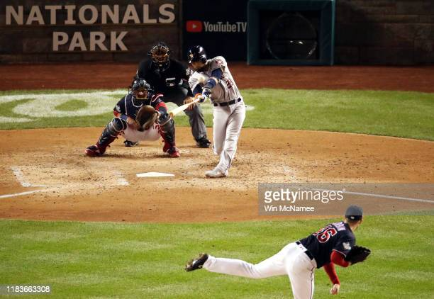 Robinson Chirinos of the Houston Astros hits a two-run home run against Patrick Corbin of the Washington Nationals during the fourth inning in Game...