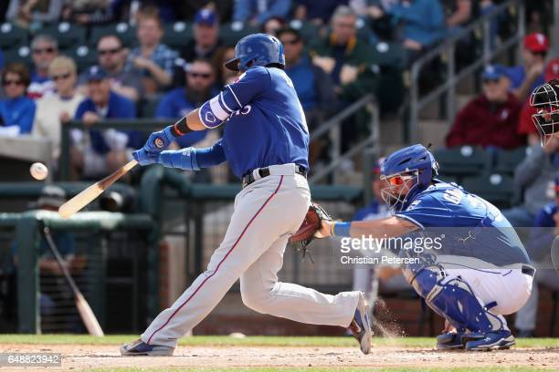 Robinson Chirinos of the Texas Rangers bats against the Kansas City Royals during the spring training game at Surprise Stadium on February 26 2017 in...