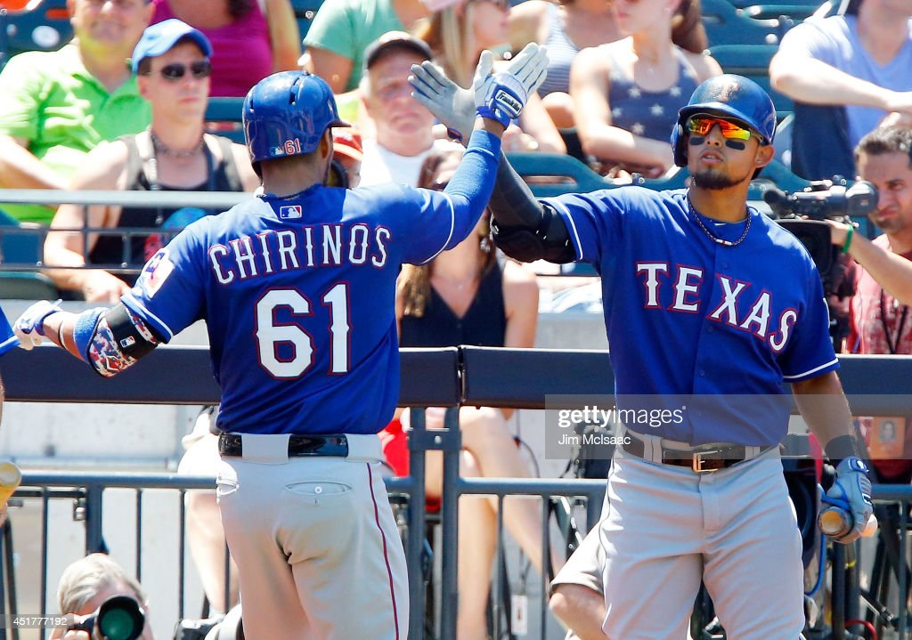 Robinson Chirinos #61 of the Texas Rangers celebrates his fourth inning home run against the New York Mets with teammate Rougned Odor #73 at Citi Field on July 6, 2014 in the Flushing neighborhood of the Queens borough of New York City.