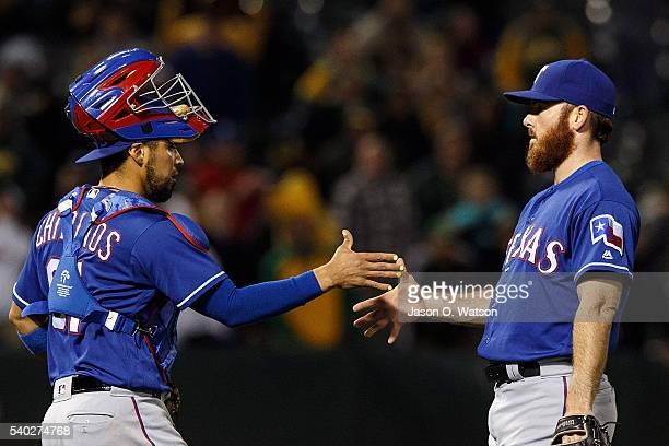 Robinson Chirinos of the Texas Rangers celebrates with Sam Dyson after the game against the Oakland Athletics at the Oakland Coliseum on June 14 2016...
