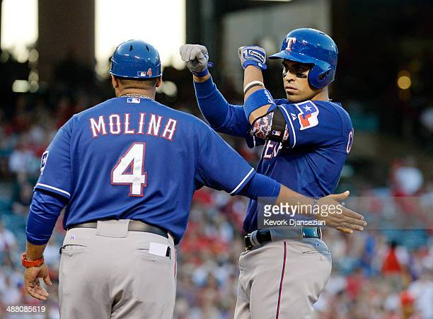 Robinson Chirinos of the Texas Rangers is congratulated by first base coach Bengie Molina after a single to score teammate Mitch Moreland in the...