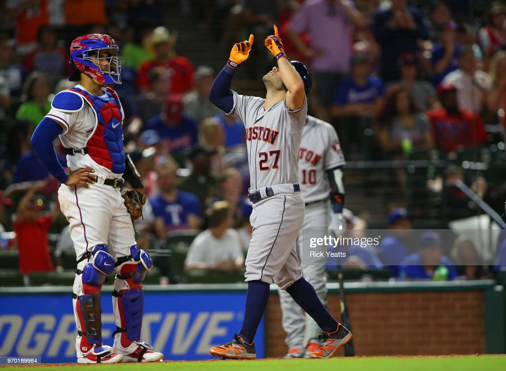 Robinson Chirinos #61 of the Texas Rangers looks one on as Jose Altuve #27 of the Houston Astros points to the sky after hitting a two run home run in the seventh inning at Globe Life Park in Arlington on June 8, 2018 in Arlington, Texas.