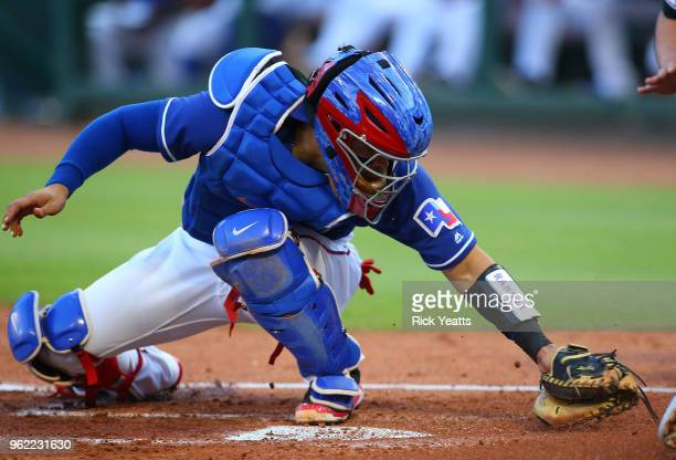 Robinson Chirinos of the Texas Rangers misses the tag at home in the second inning against the Kansas City Royalsat Globe Life Park in Arlington on...