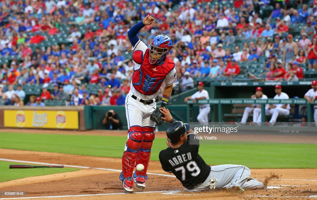 Robinson Chirinos #61 of the Texas Rangers misses the tag on Jose Abreu #79 of the Chicago White Sox at Globe Life Park in Arlington on August 19, 2017 in Arlington, Texas.