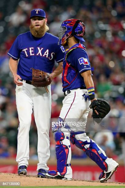 Robinson Chirinos of the Texas Rangers talks with Andrew Cashner of the Texas Rangers on the mound in the top of the fourth inning against the...