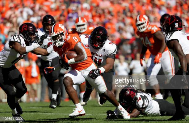 G Robinson of the Louisville Cardinals tries to stop Travis Etienne of the Clemson Tigers as he runs for a touchdown against the Louisville Cardinals...