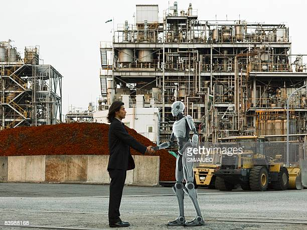 Robot and human greeting in front of factory