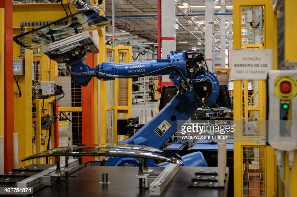 A robot arm carries a glass part in the assembly line of the March and Versa models at Nissan's Industrial Complex in Resende 160 km west of Rio de...