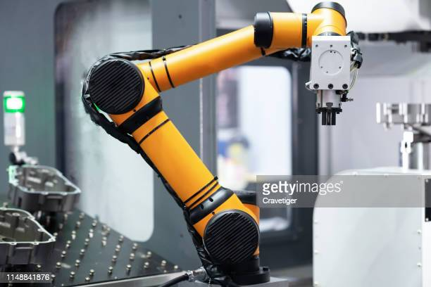 robot arm 's going to pick parts to cnc machine in the manufacturing factory. - robot stock pictures, royalty-free photos & images