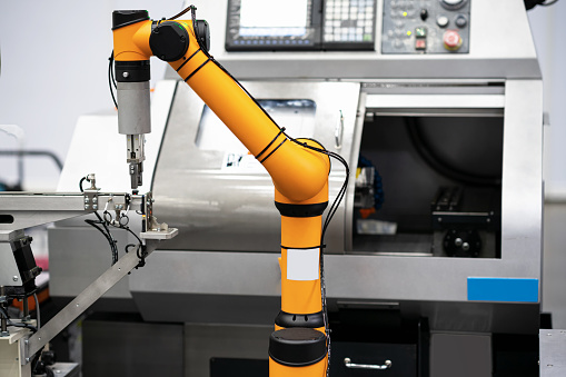 Robot arm 's going to pick parts to CNC machine in the manufacturing factory. - gettyimageskorea