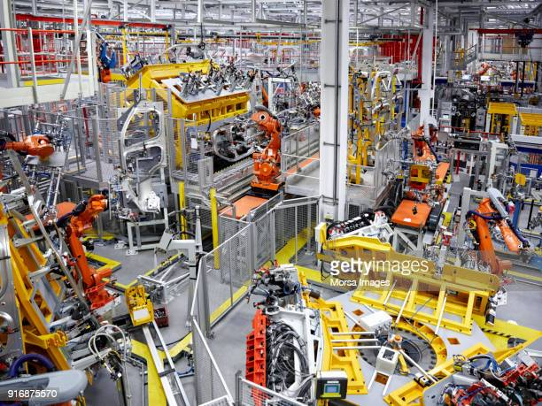 robot arms in a car manufacturing factory - automated stock pictures, royalty-free photos & images