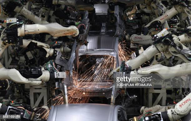 Robot arms weld the bodies of fourth generation Toyota Prius cars on the production line at the company's Tsutsumi assembly plant in Toyota City,...