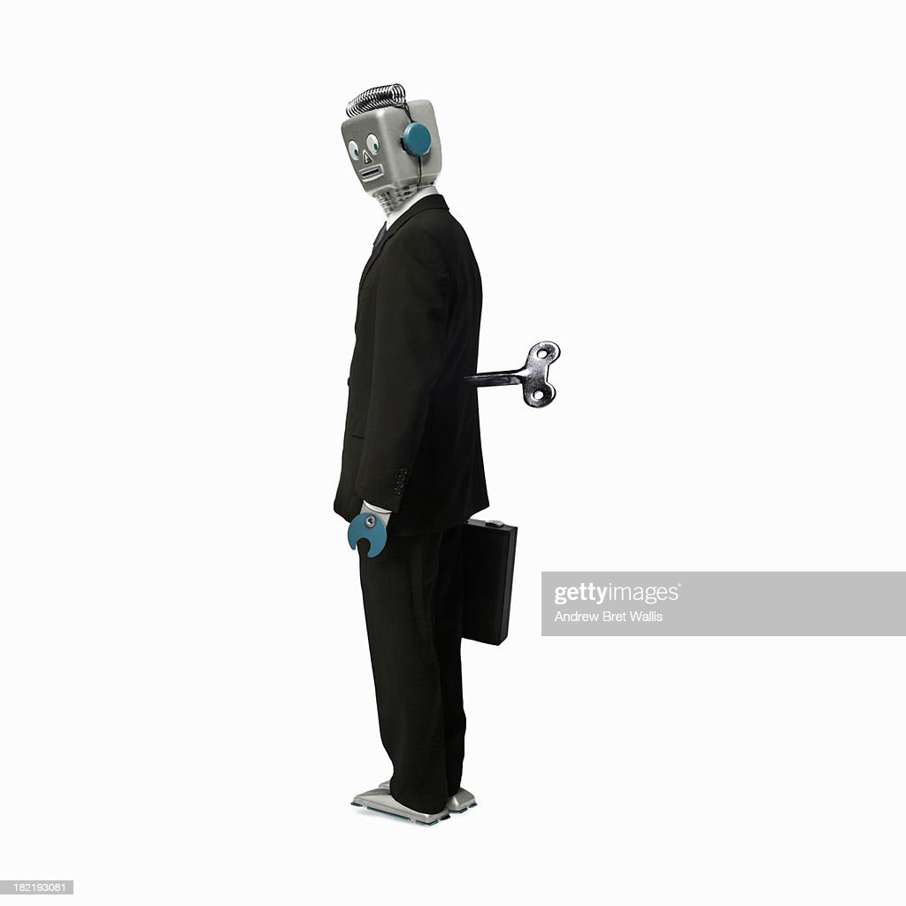 Robot businessman stands with a key in his back : Stock Photo