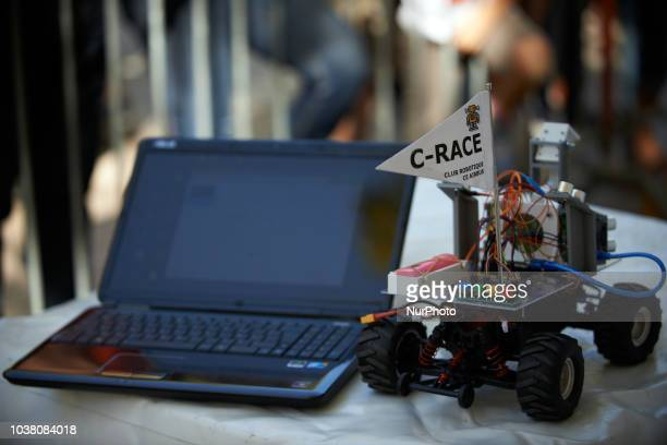 A robot car and a laptop to program it during the race A robots race took place in Toulouse Machines are either cars or walking robots They were...