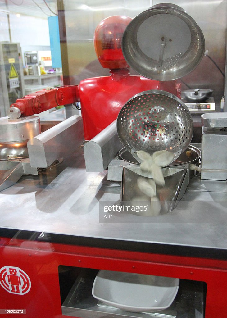 A robot cooks dumplings in a robot-themed restaurant in Harbin, northeast China's Heilongjiang province on January 16, 2013. Twenty robots perform a variety of chores, from ushering in guests to waiting tables and cooking dishes. CHINA
