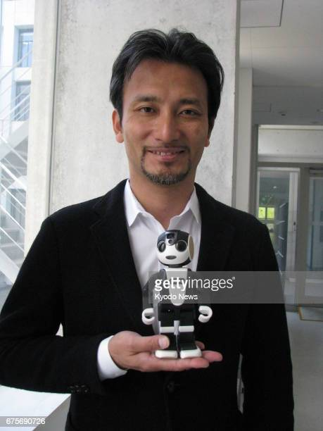 Robot developer Tomotaka Takahashi smiles with his partner RoBoHoN after an interview in his office at the University of Tokyo on April 14 2017...