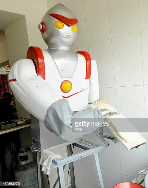 A robot dressed as superman 'Ultraman' slices noodles at a restaurant on April 26 2011 in Shenyang Liaoning Province of China The restaurant owner...